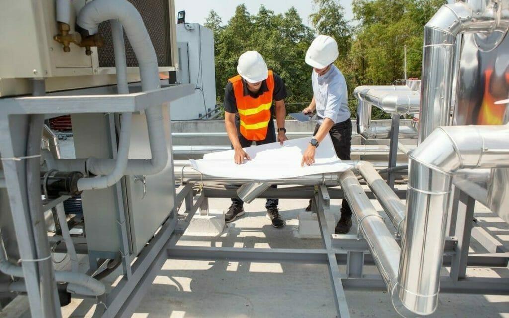 Zwei Ingenieure mit Plan neben Rohren auf Dach